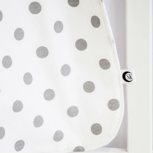 grey and white polka dot baby blanket on white crib