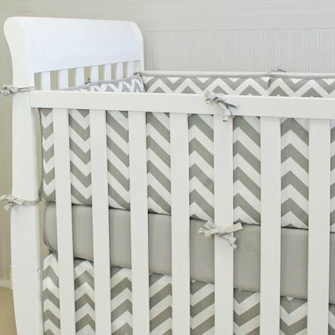 grey and white zigzag baby bumpers, grey sheet, crib skirt on white crib