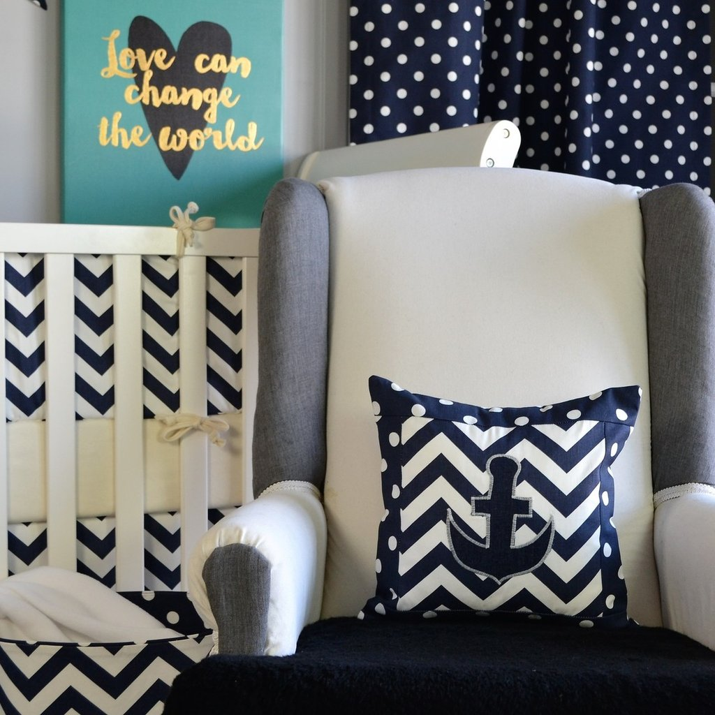 navy and white zig zag anchor pillow on white chair with white crib