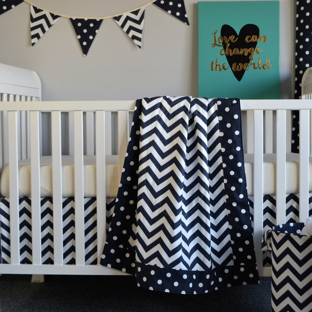 navy and white zig zag blanket and skirt with varsity flags on white crib