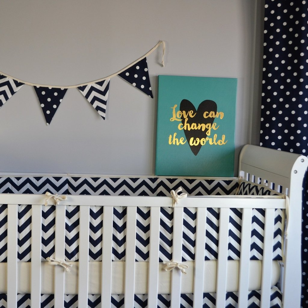 navy and white zig zag bumper with varsity flags on a white crib