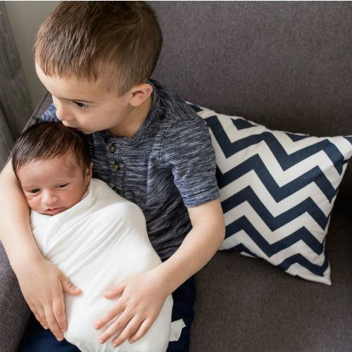 navy and white zig zag lumbar pillow with big brother kissing baby brother