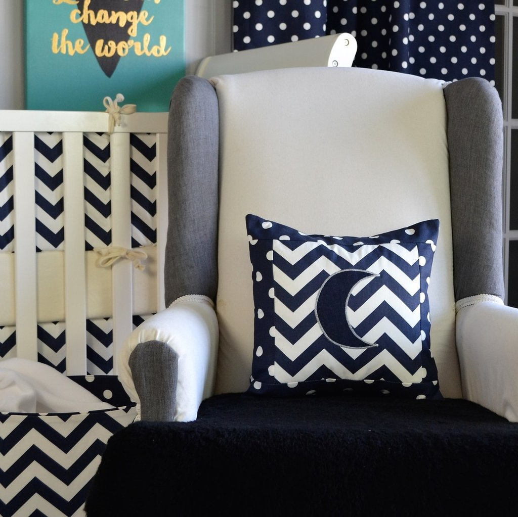 navy and white zig zag moon pillow on white chair with white crib
