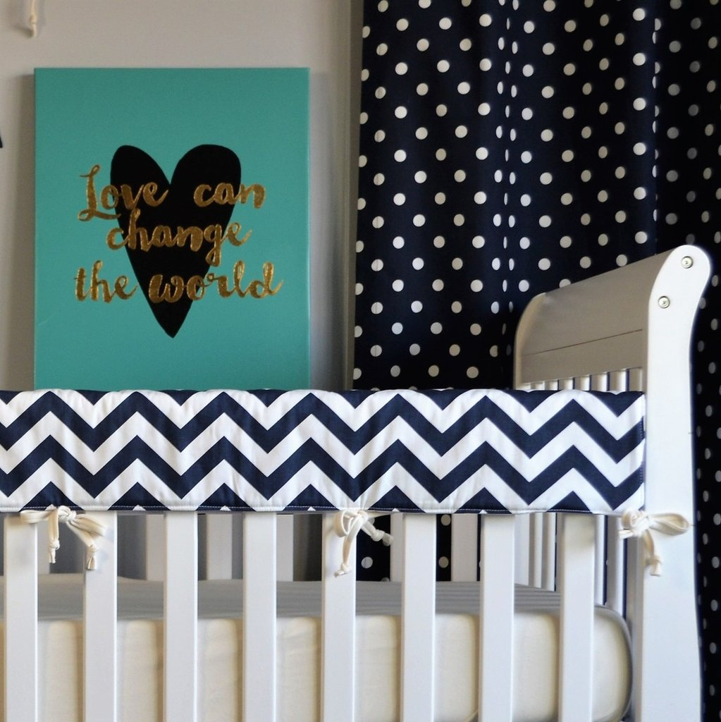 navy and white zig zag rail protector on white crib with dot drapes