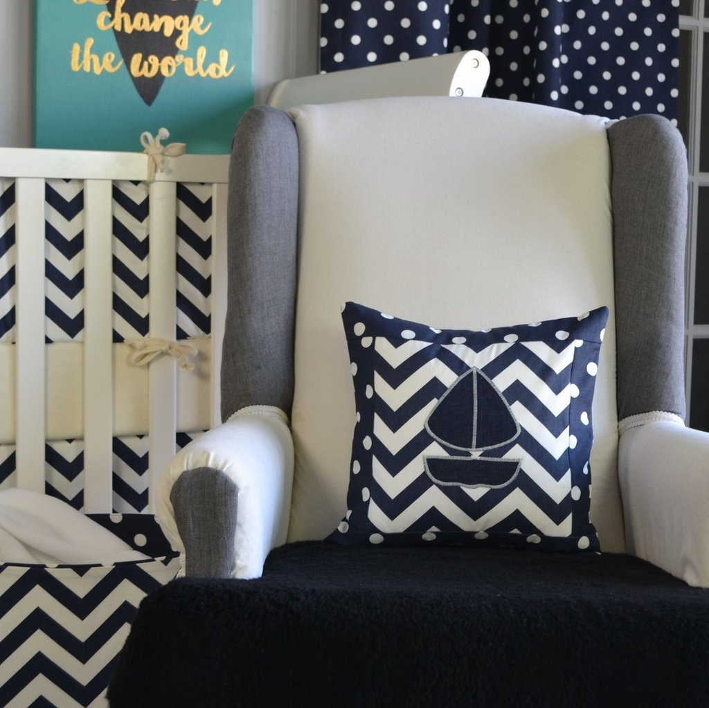 navy and white zig zag sailboaty pillow on white chair with white crib