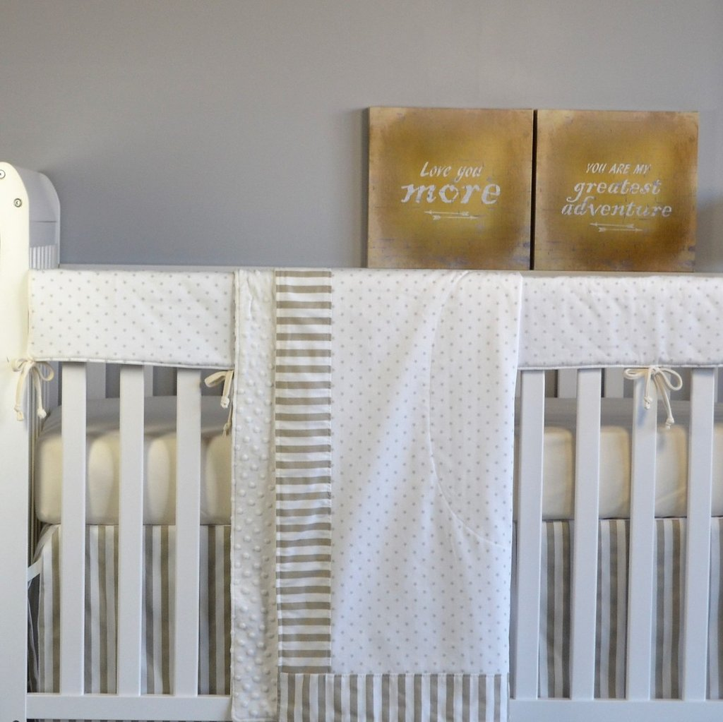 white blanket with mini grey stars hanging on crib set with white rail protector