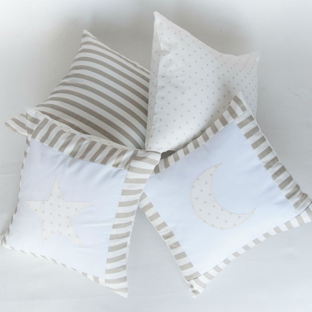 multiple decor pillows in a pile with moon and star pattern