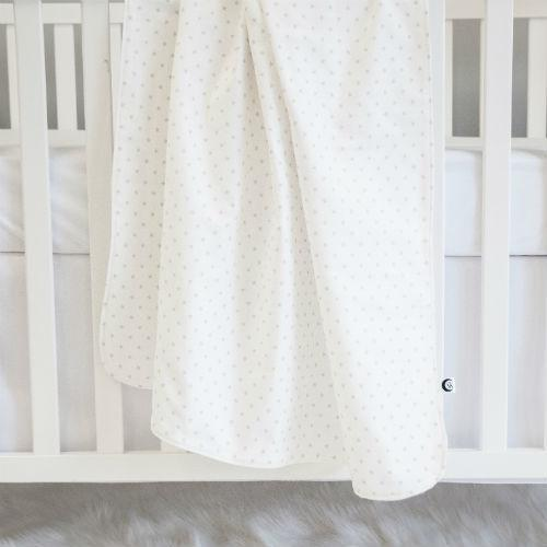 large white blanket with mini star pattern hanging over crib rail