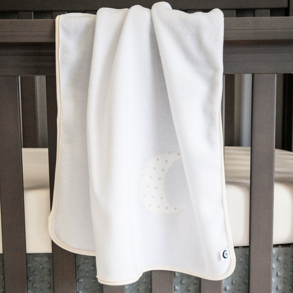 white blanket with moon pattern hanging over crib rail