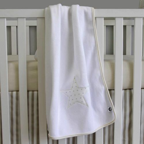 white blanket with big grey star on it hung over crib rail
