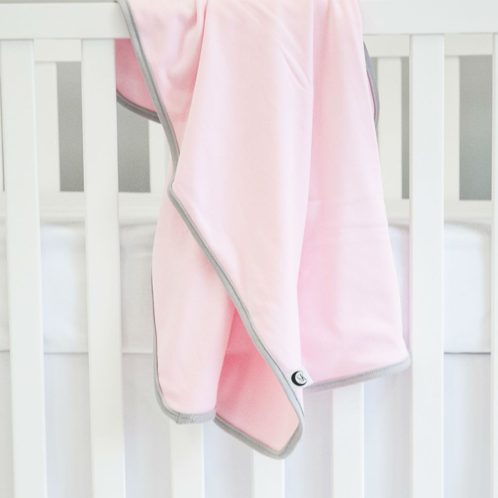 swaddle blanket pink with grey trim on white crib