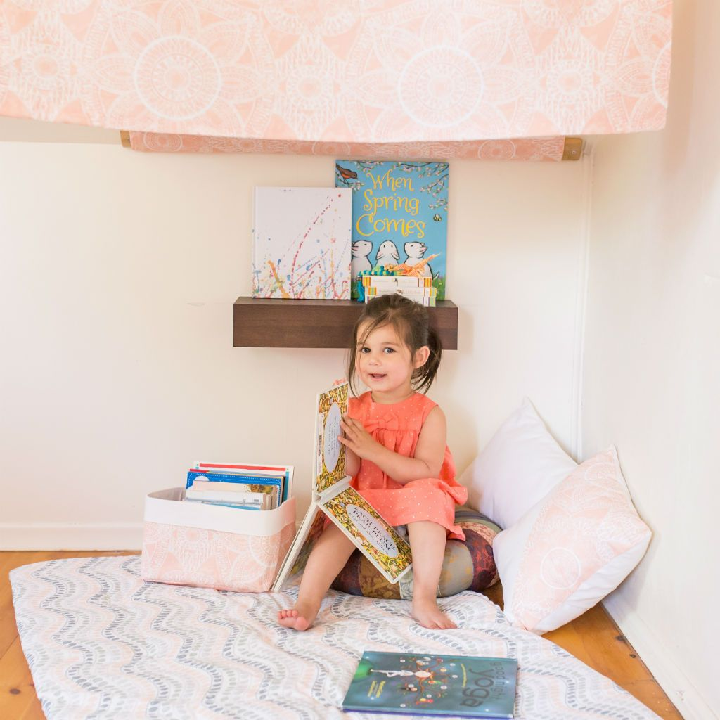 sweet toddler reading a book in nook with play blanket and canopy