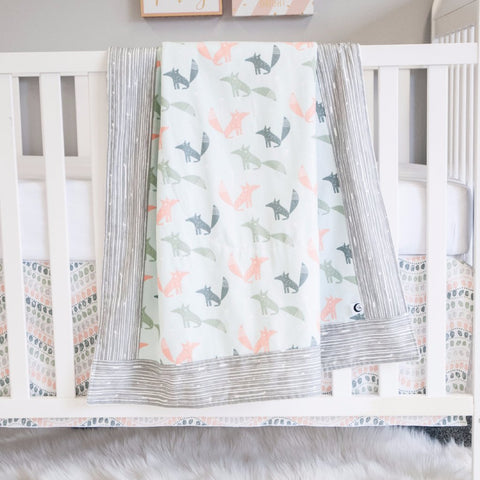 white crib with jewel pattern crib skirt, fox pattern blanket and white crib sheet
