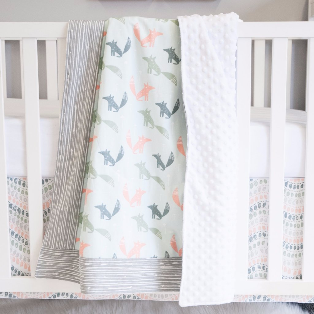 coral, dark teal and grey jewel patterned fox blanket with grey bark border on white crib