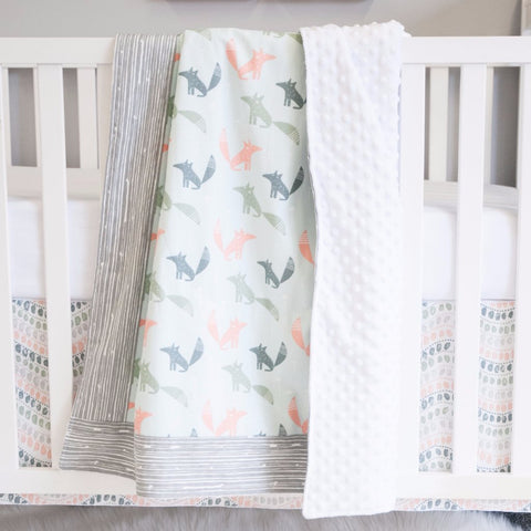 coral, dark teal and grey fox pattern blanket hanging from a white crib