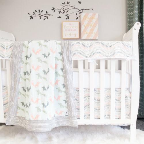 crib with woodland fox blanket, rail protector, crib skirt, and crib sheet