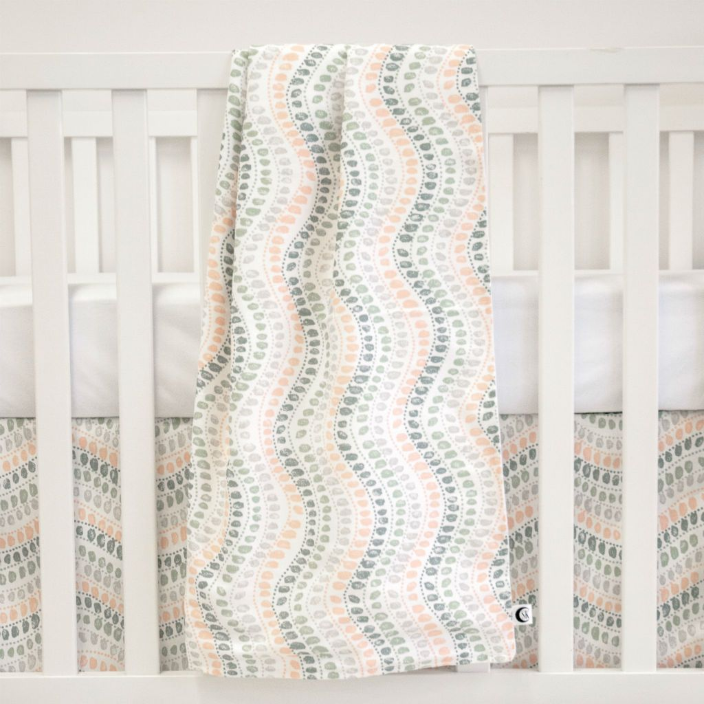 white crib with coral, dark teal and grey jewel patterned blanket hanging