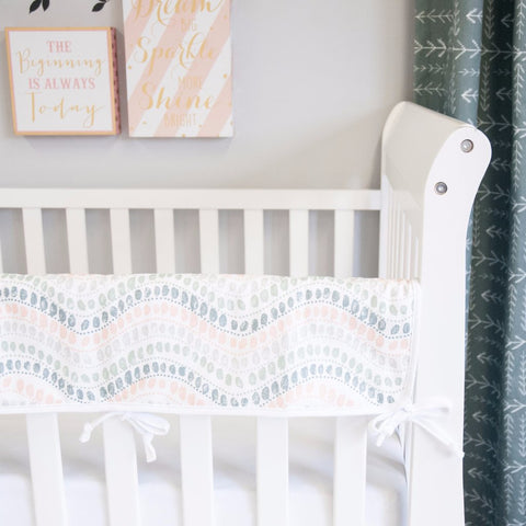 jewel patterned rail protectors on a white crib