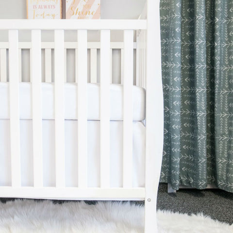 white crib with white crib sheet and white crib skirt