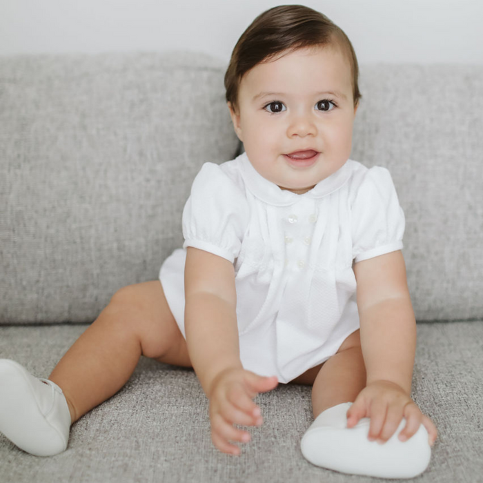 White baby piqué romper with peter pan collar and cap sleeves