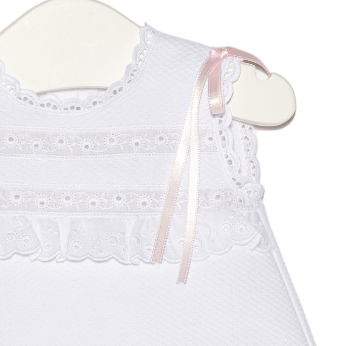 White newborn Maria pique dress with embroidered frill details and pink satin ribbons