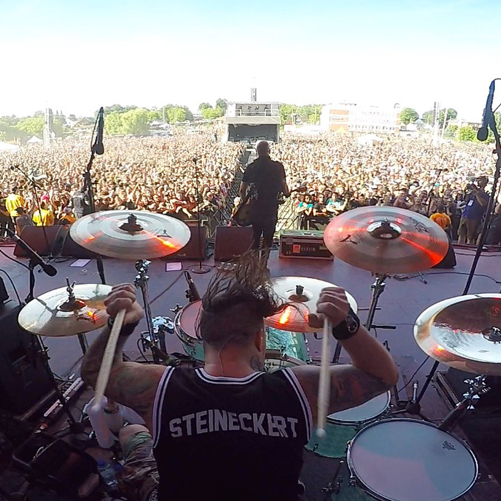 Brandon Steineckert playing drums in the band Rancid in front of a giant crowd.