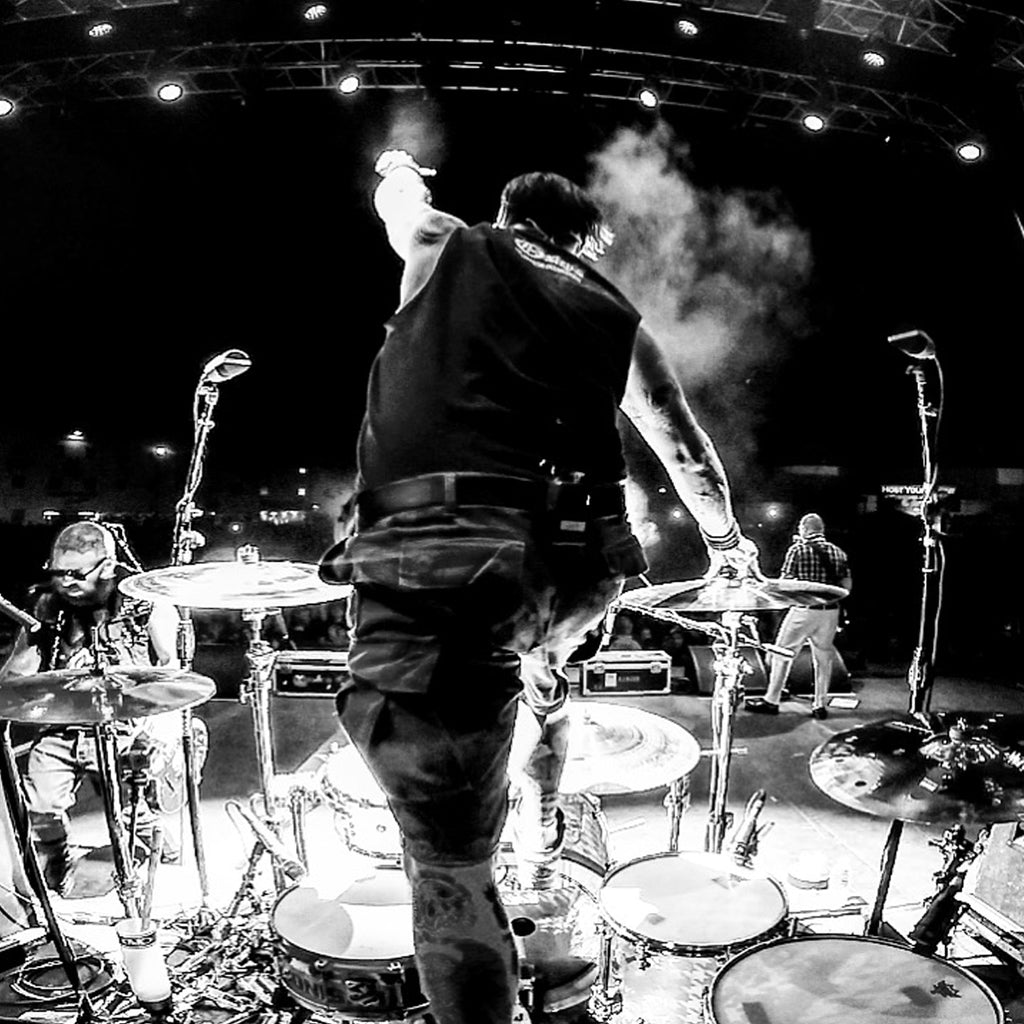 Black & white photo of Brandon Steineckert climbing on his drums during a concert.