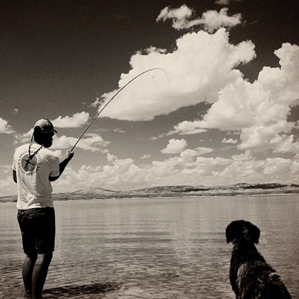 Colby Crossland with a big fish on the line and his dog Forelle looking on.