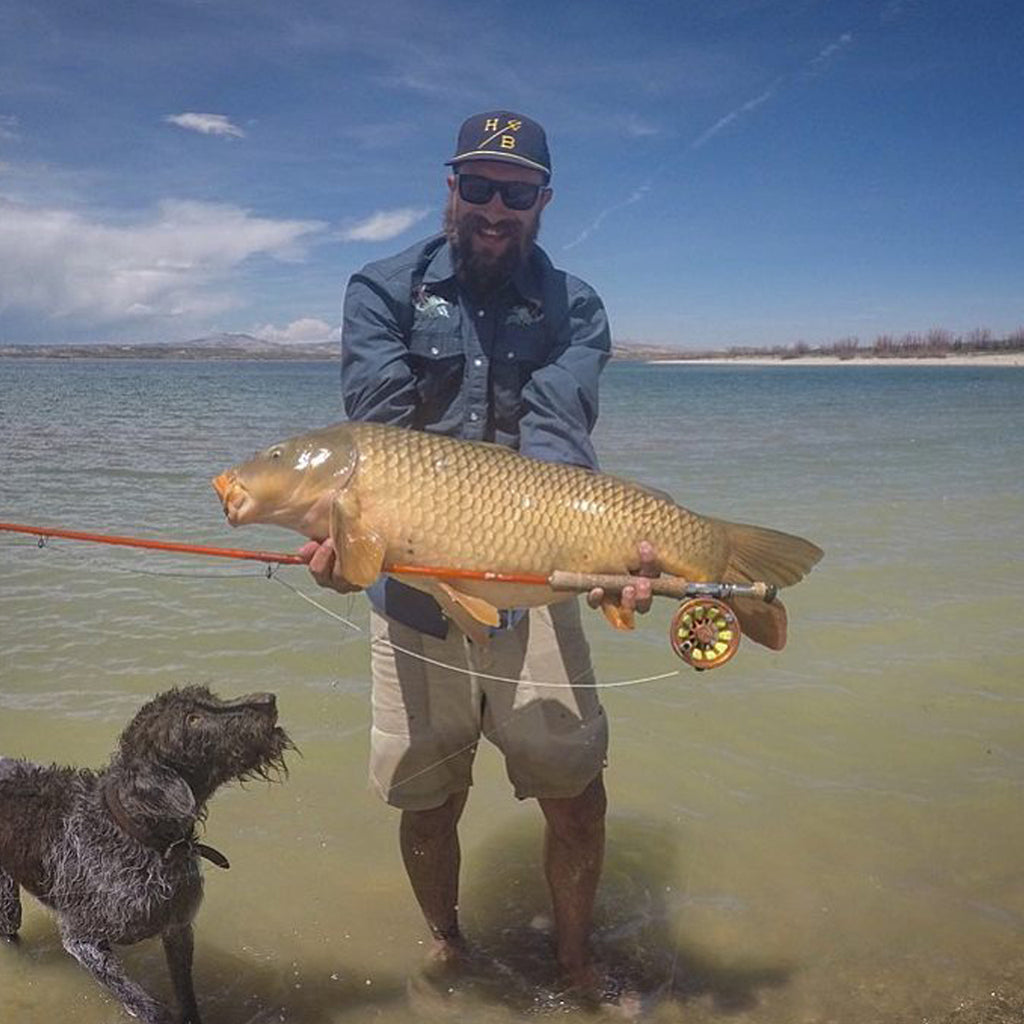 Colby Crossland holding a large fish with his dog Forelle in the water next to him.