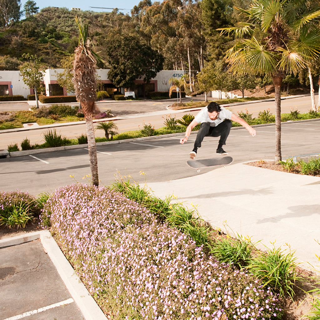 Corey Duffel doing a huge kickflip on his skateboard over a flower bed.
