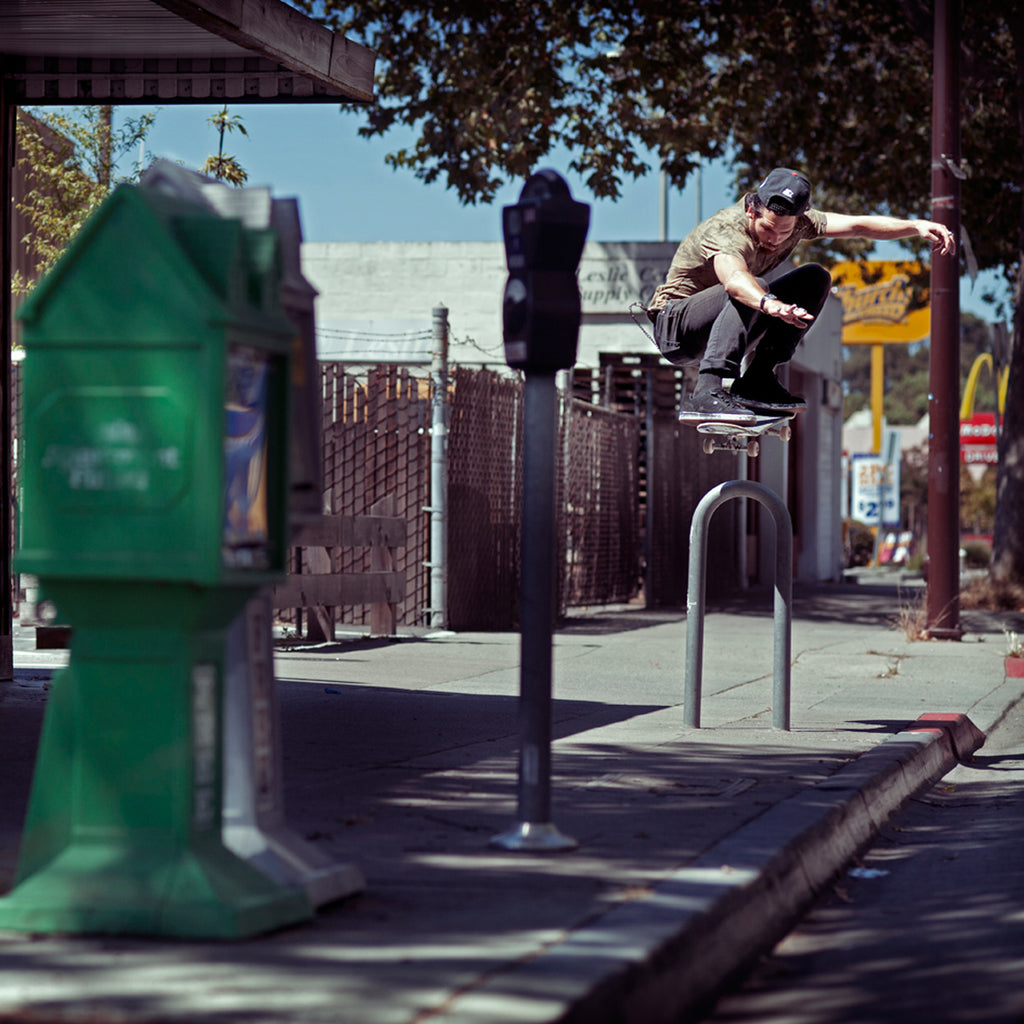 Corey Duffel doing an ollie on his skateboard over a bike rack on the sidewalk.