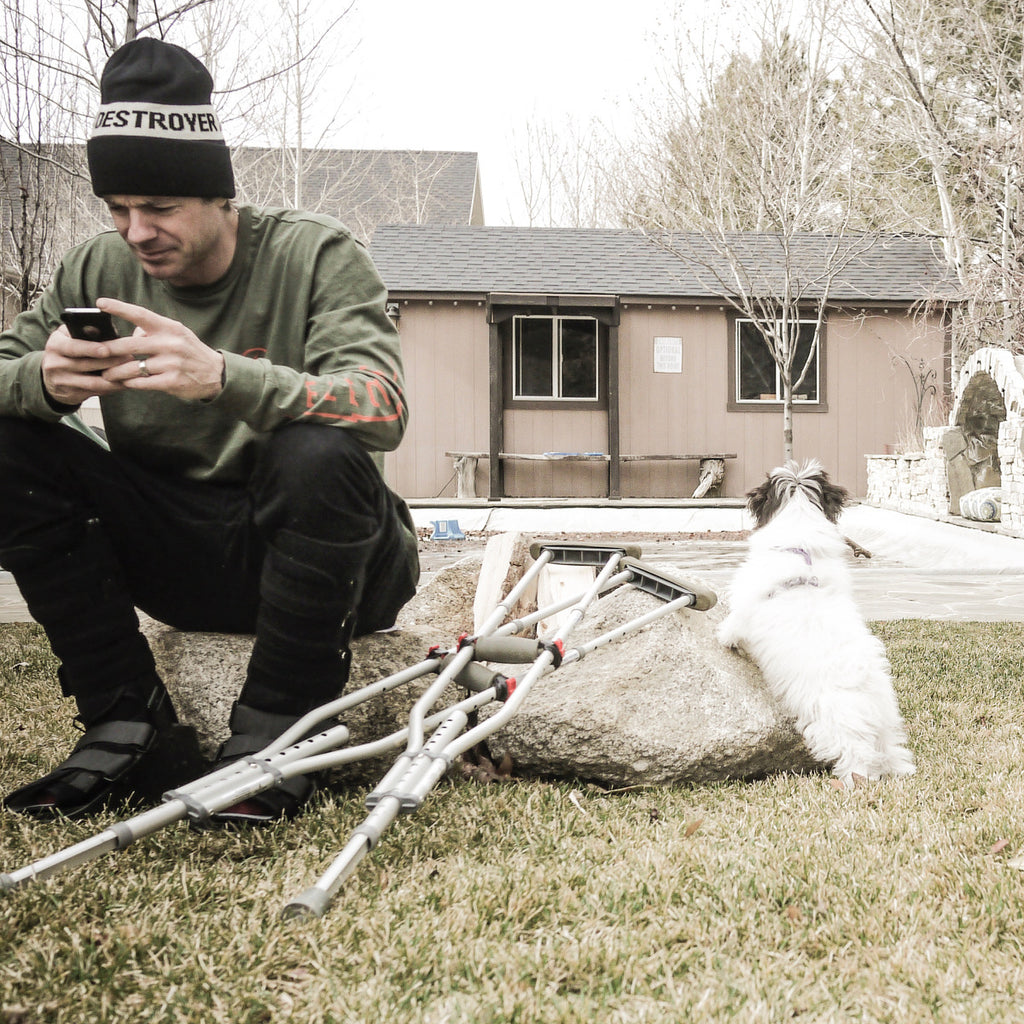 Jeremy Jones sitting in his backyard with his crutches and his dog Mozzy.