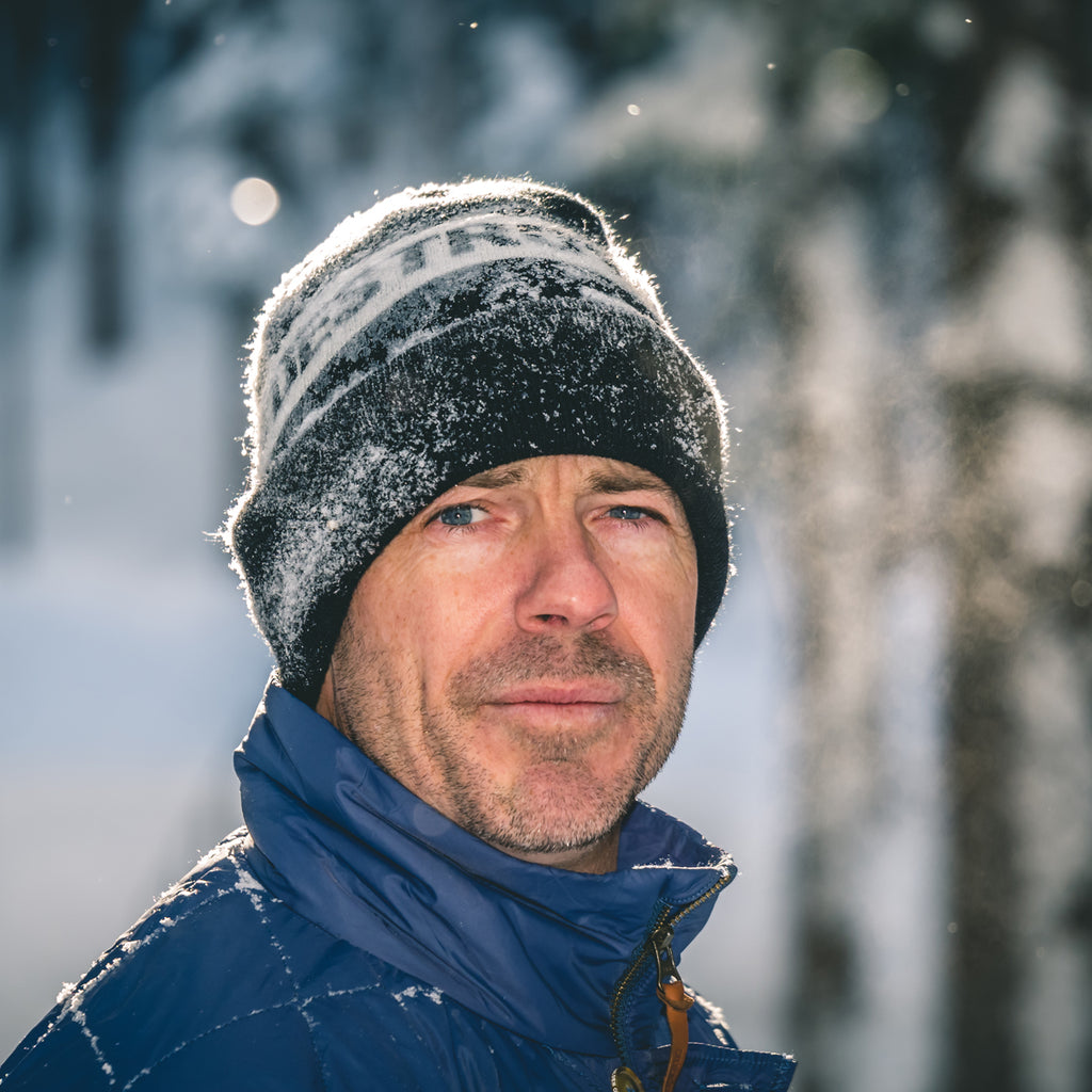 Jeremy Jones portrait wearing a beanie with snow falling.