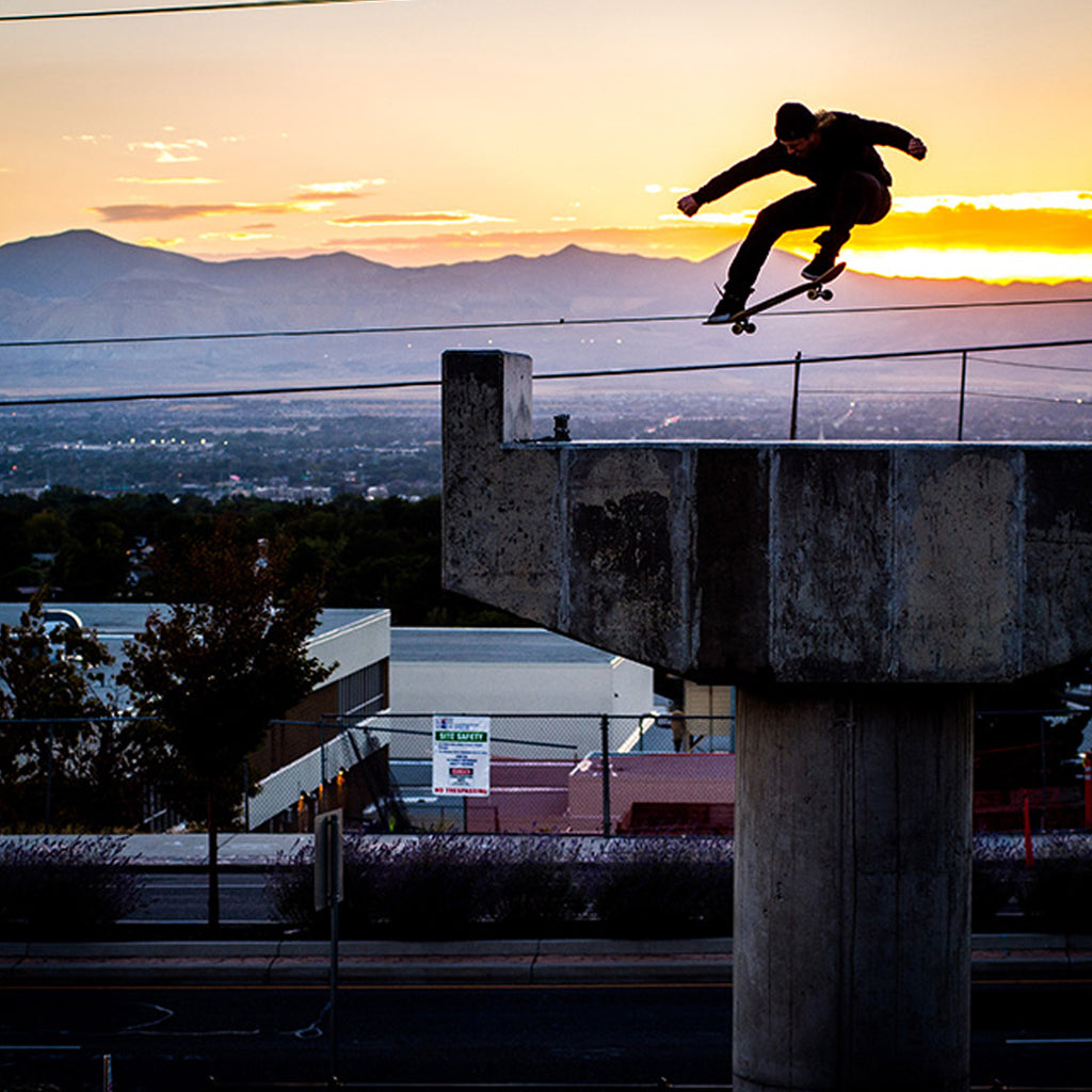 Jeremy Jones doing an ollie over a handrail on his skateboard with a sunset in the background.