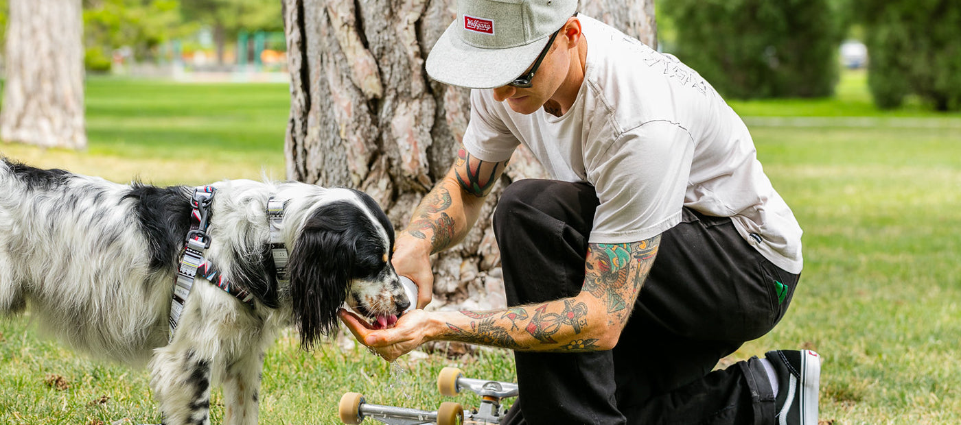 Pro snowboarder Pat Moore with his dog and skateboard in the park. Links to Wolfgang look book.