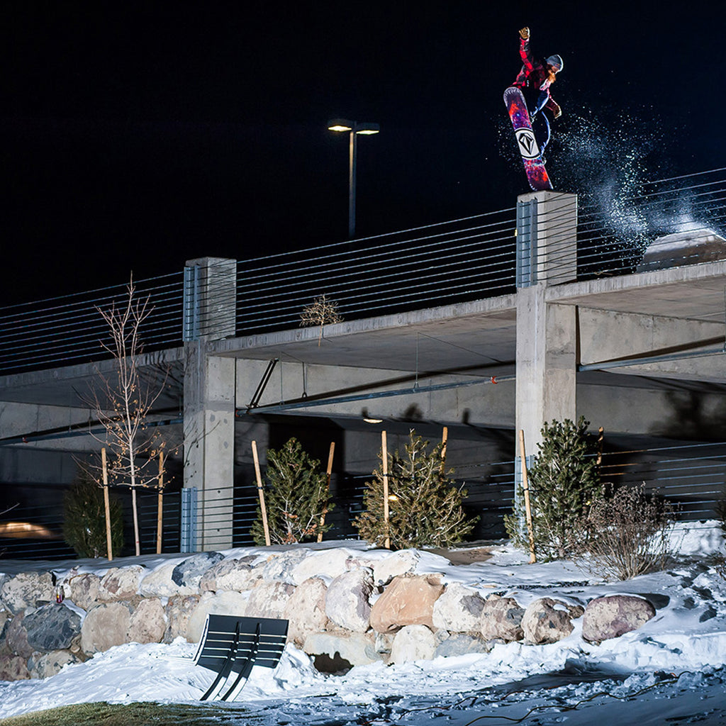 Night shot of Pat Moore jibbing off a parking building on his snowboard.