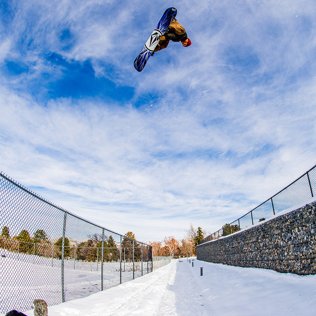 Pat Moore spinning a huge indi air over two fences on his snowboard.