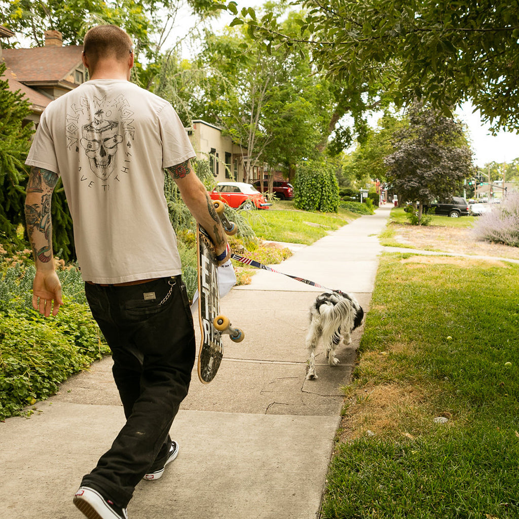 Pat Moore walking on a sidewalk with his dog Murphy carrying his skateboard.