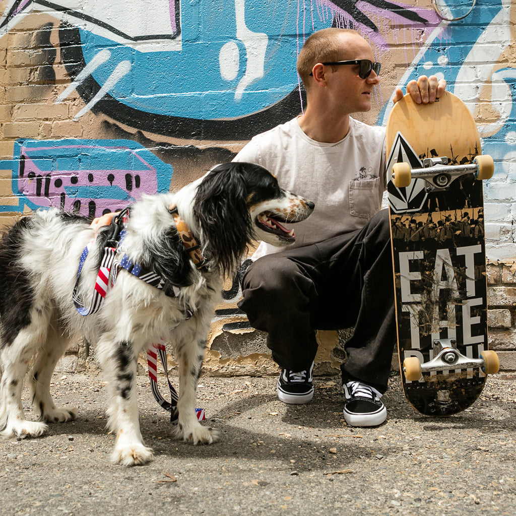 Pat Moore crouching down holding his skateboard with his dog Murphy.