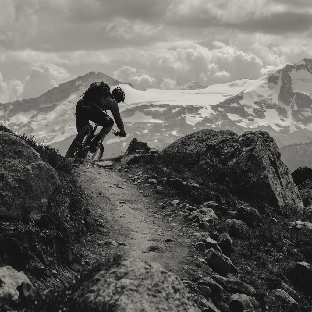 Eric Porter riding his mountain bike on a rocky trail with snowy mountains in the background.