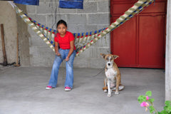 Brite Blue Guatemalan girl in hammock with dog