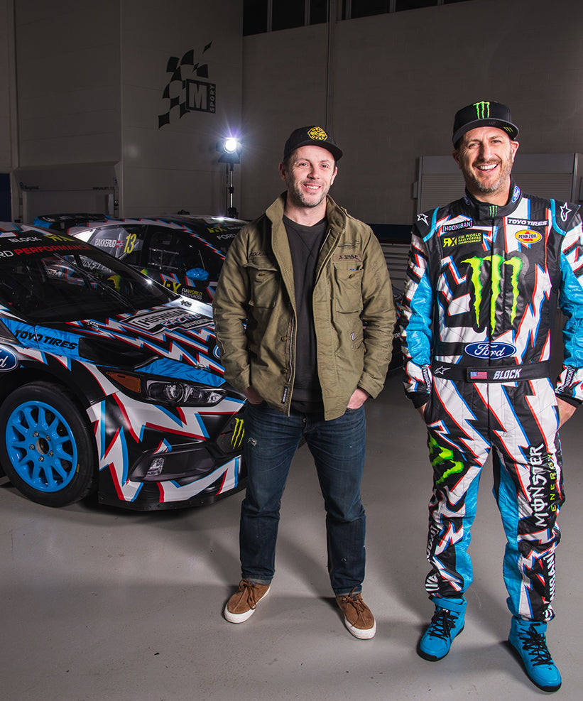 Ken Block in race suit designed by Death Spray Custom in front of Ford Focus rally car.