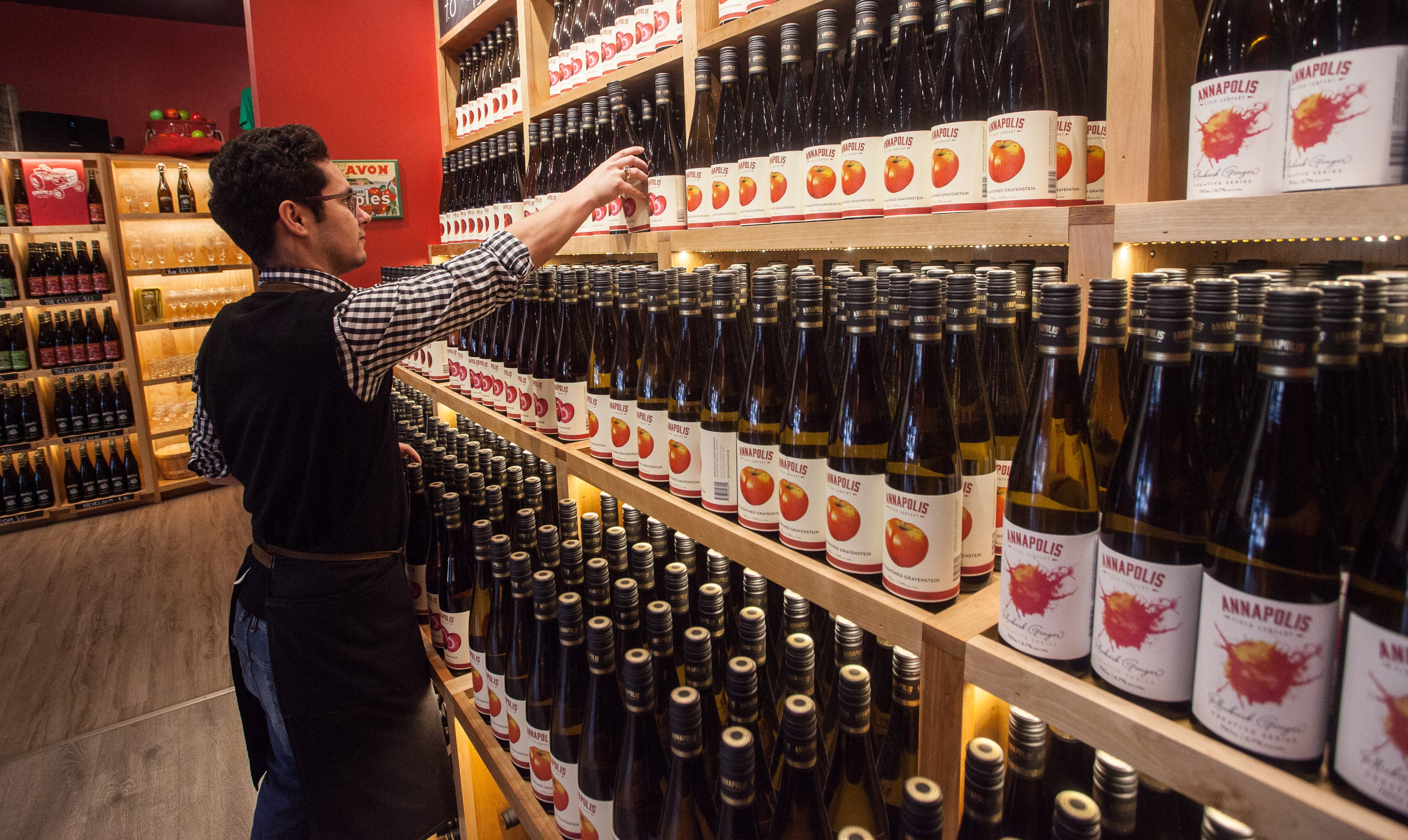 A worker stocks the shelves at the Annapolis Cider Company.