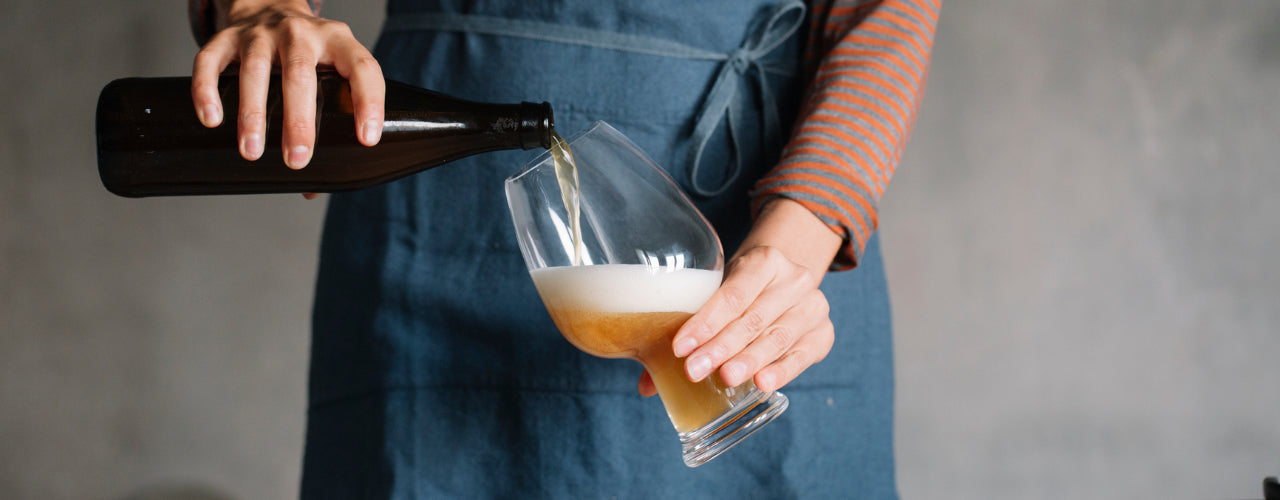 A person pours a glass of homemade beer.