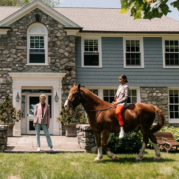 Photo of two women on horses in front of a light blue house