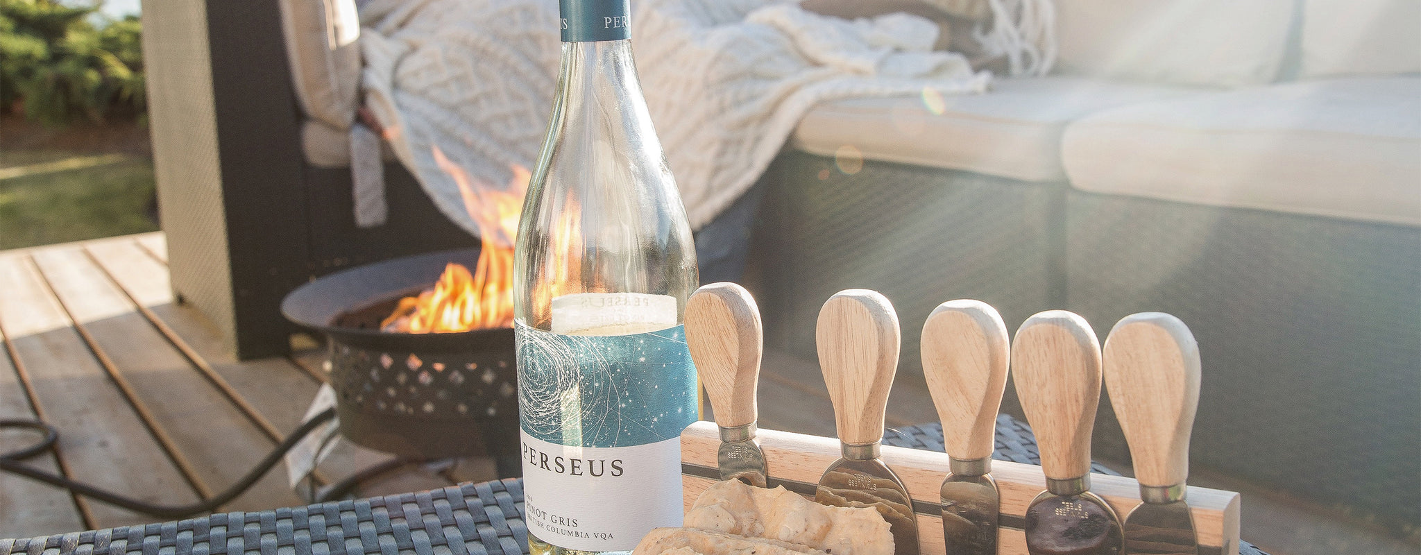 Photo of a white wine bottle on an outdoor table next to a small fire
