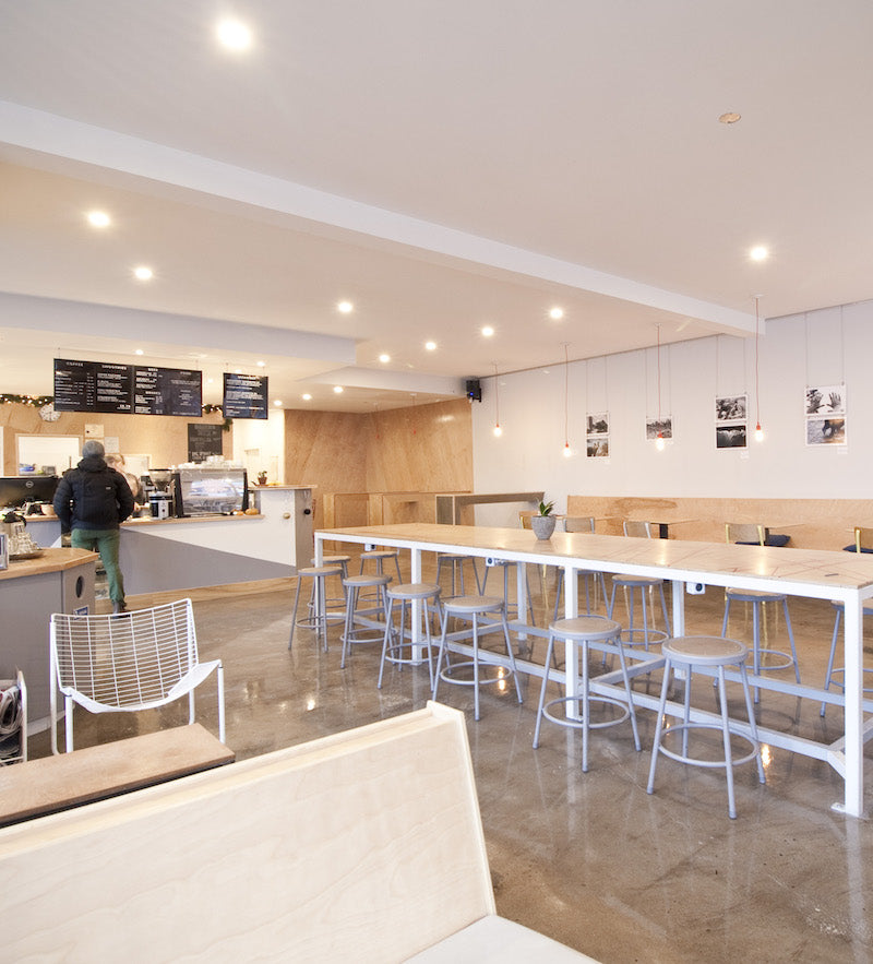 Photo of the interior of Seven Bays Cafe with white walls and light wood furniture