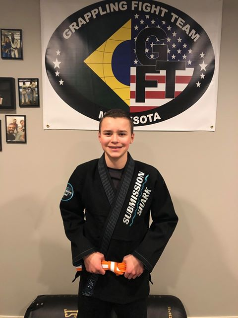 Youth BJJ Practitioner That Is Happy In a Black Submission Shark Jiu Jitsu Gi