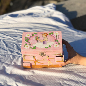 Ballet School Music box top view in sunshine | A ballerina is on top in pink with a posey and morning glories around her.  Scenes from the ballet studio are on the side.  Watercolor illustrations and 4 secret corner treasure drawers | Pretty musical gifts for kids from Enchantmints