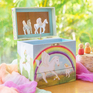 Pegasus rainbow music box on table with silks and wooden toys | Musical treasure boxes and decor for kids from Enchantmints | unusual gifts for girls